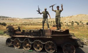 Syrian rebel fighters pose on a destroyed tank