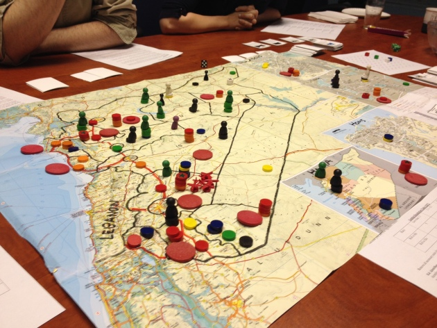 Using a modified commercial map for the initial game board. The large red disks are Syrian airfields and divisional bases; the smaller red risks are regular Syrian army units (elite units denoted by a star); the red aircraft indicate airstrikes; and the orange disks denote shabiha, National Defence Force, and other pro-regime militias. The black, green and white disks denote FSA, Islamist, and Kurdish militias, while the avatars represent key opposition commanders. The remaining disks (yellow, blue) represent unaffiliated guerillas. Each province is a separate zone for movement and combat, with each of the major cities (Damascus, Homs, Hama, Aleppo) also comprising a zone unto itself. The red lines mark key lines of communication, and the Syrian desert is a separate zone with restrictions on movement.