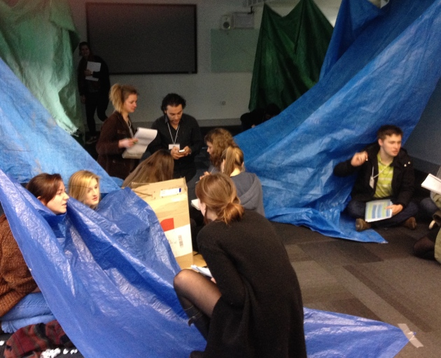The refugees sit in their make-shift shelters while aid workers undertake a needs assessment. (Exeter)