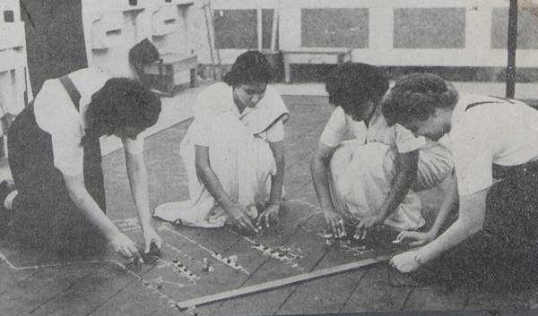 Bombay Tactical Unit WRINS plotting ship movements on the floor. Two are wearing saris, two are westerners in tropical rig.